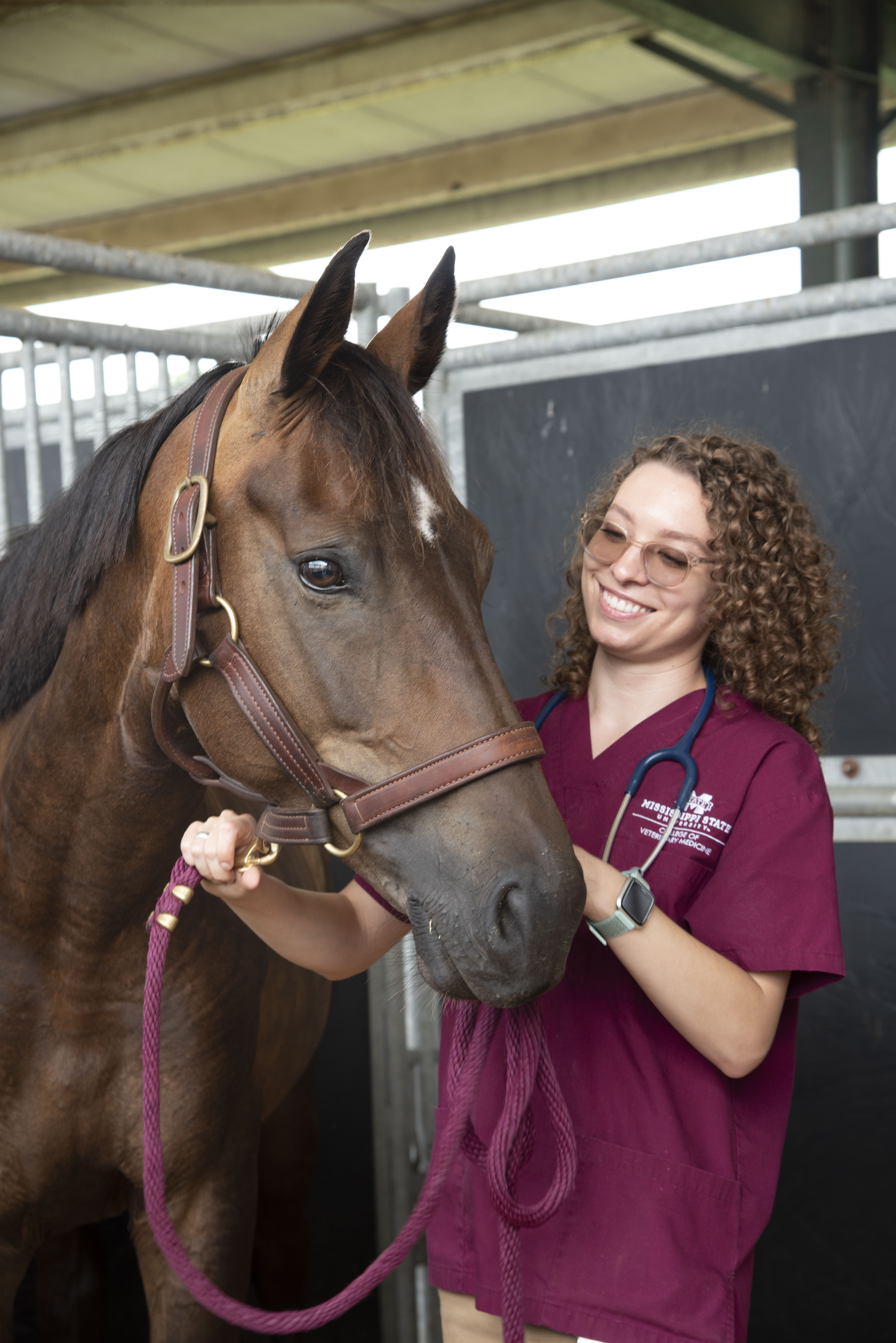 A veterinary student poses with a horse