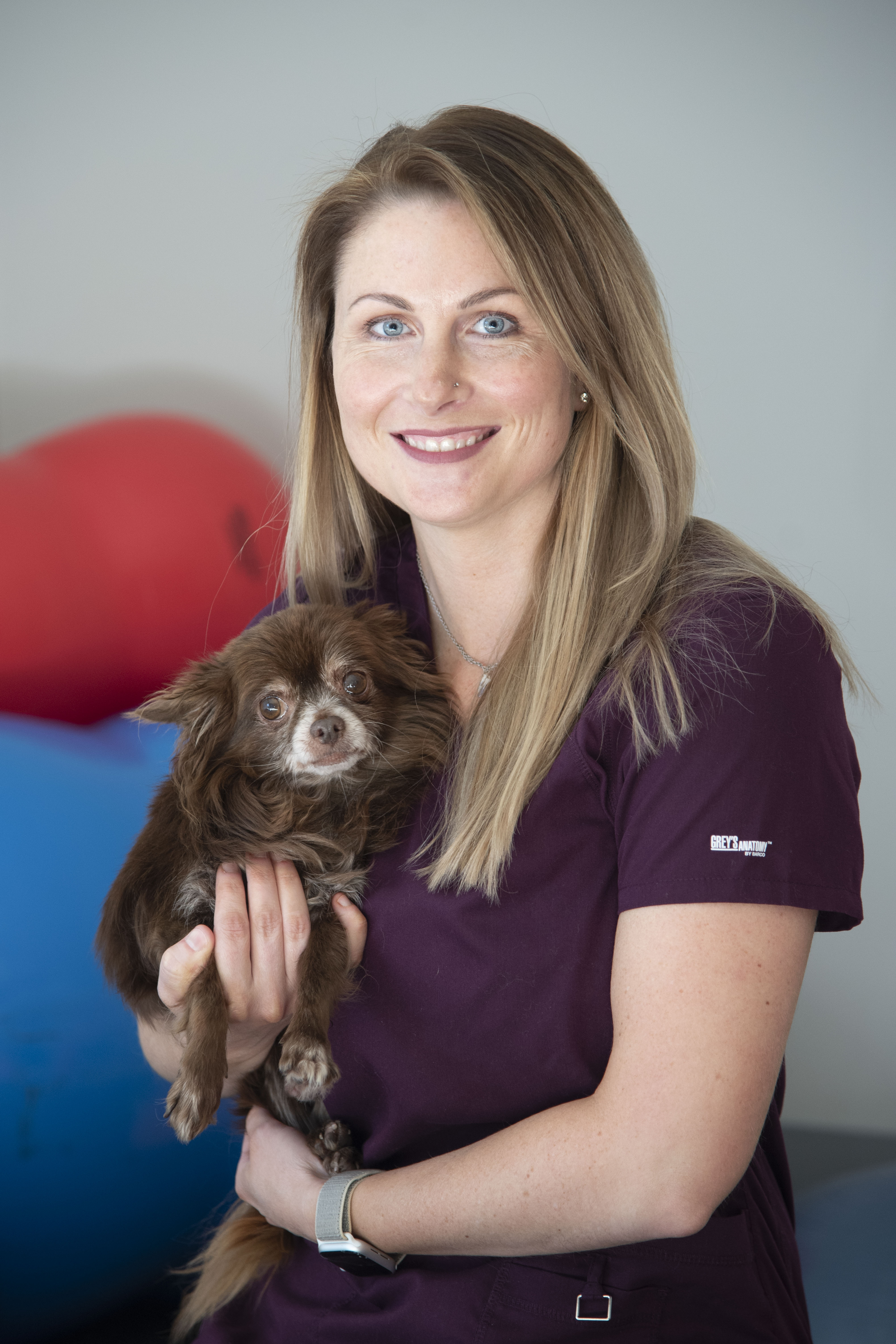 A veterinarian poses with a dog