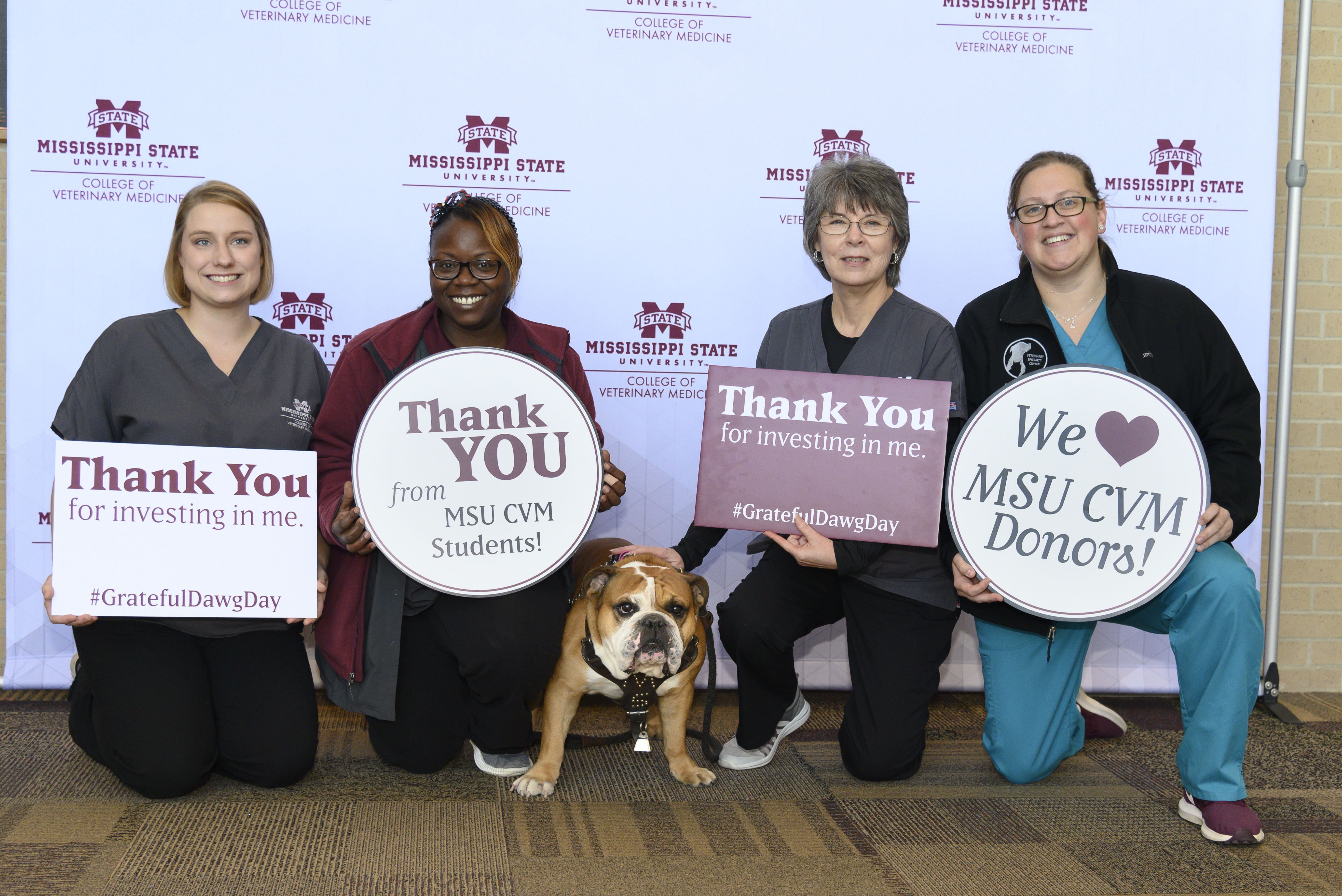 Four people pose with thank you signs and a bulldog